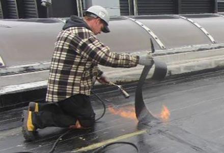 Un travailleur effectue la pose d'une membrane élastomère